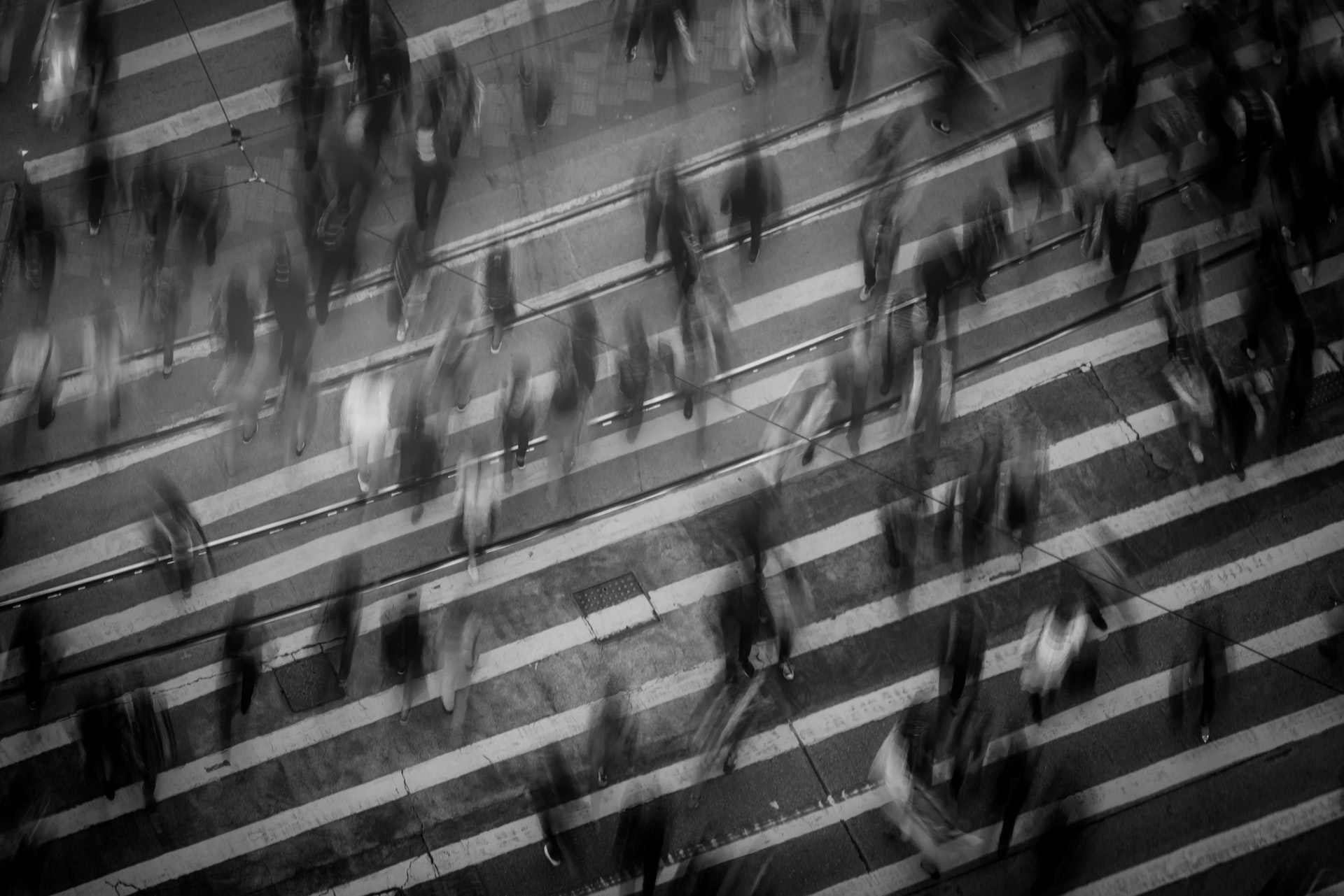 Blurred image of a crowd of people walking across the street