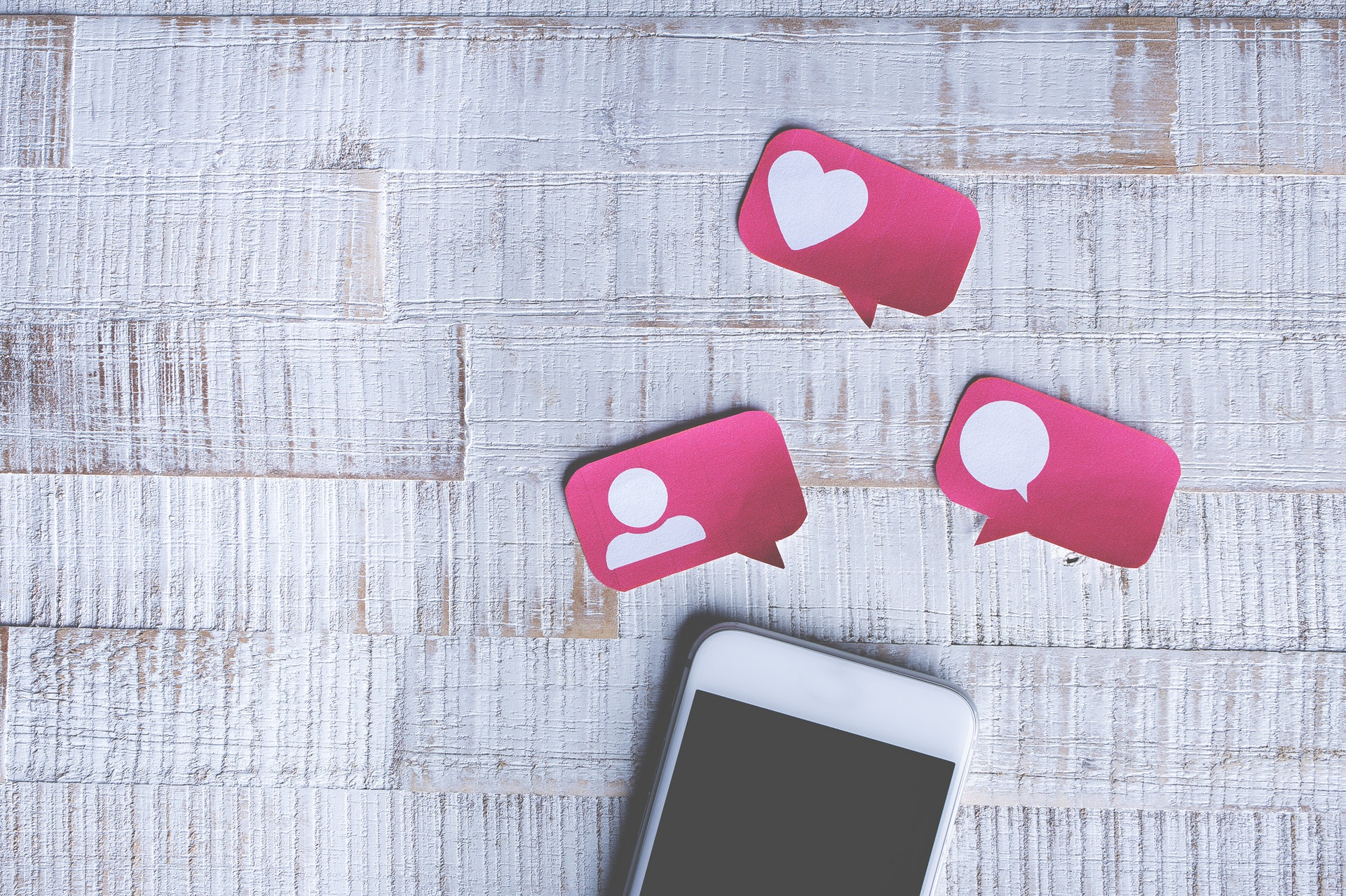 Cell phone on desk with social media likes and hearts icons