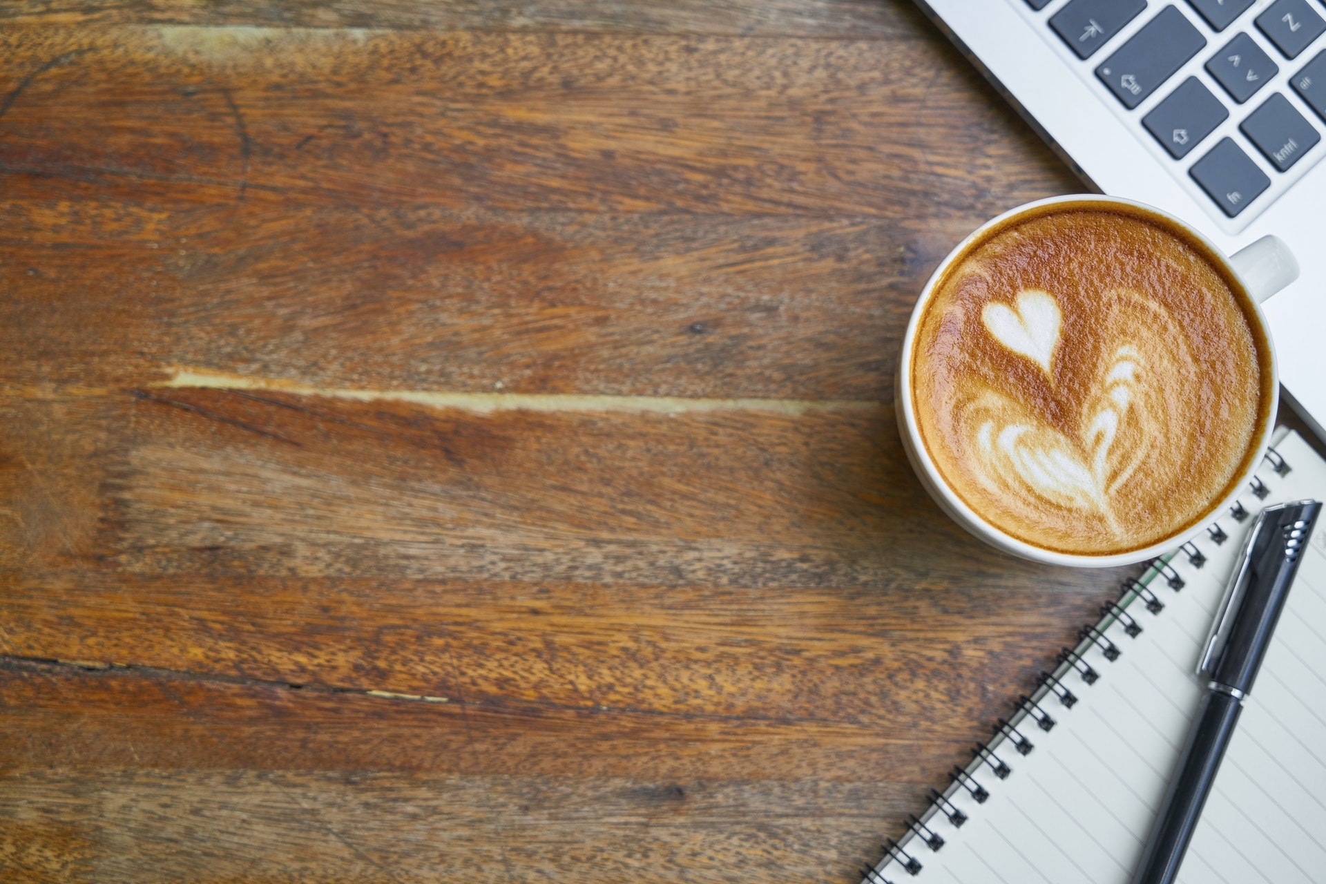 Cup of coffee next to laptop and notepad