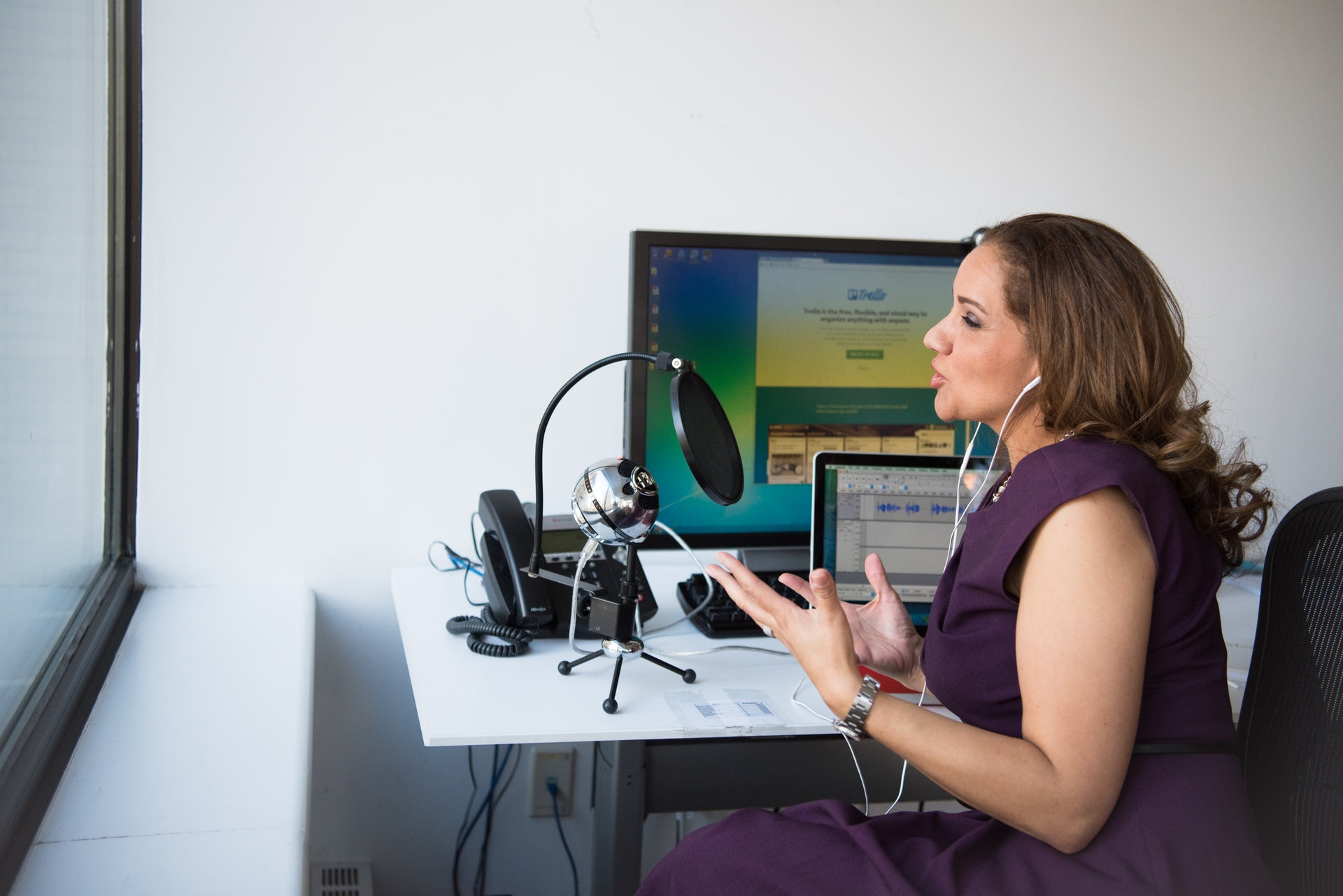 Female real estate agent in purple dress recording a podcast