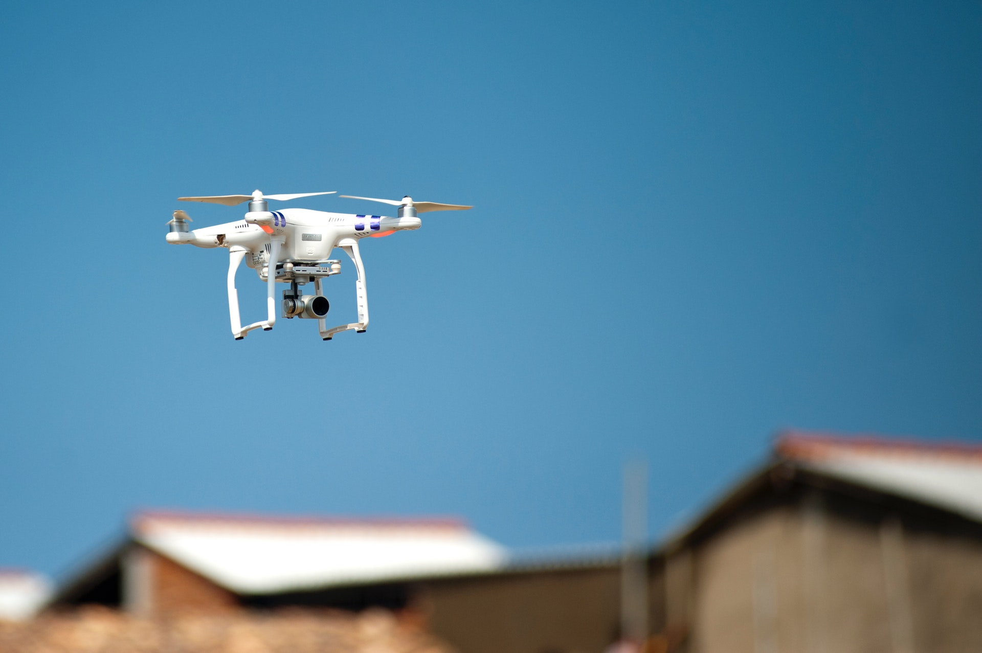 Flying drone taking pictures and recording video of houses