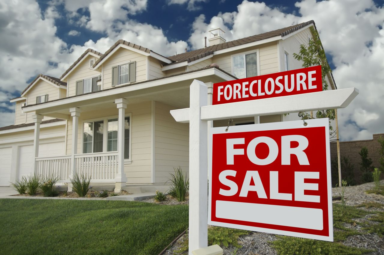 Foreclosure for sale sign on front lawn of house