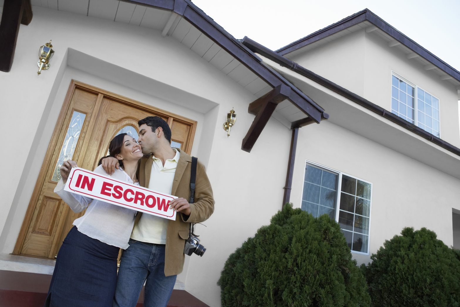 Home buyers standing in front of house that is in escrow
