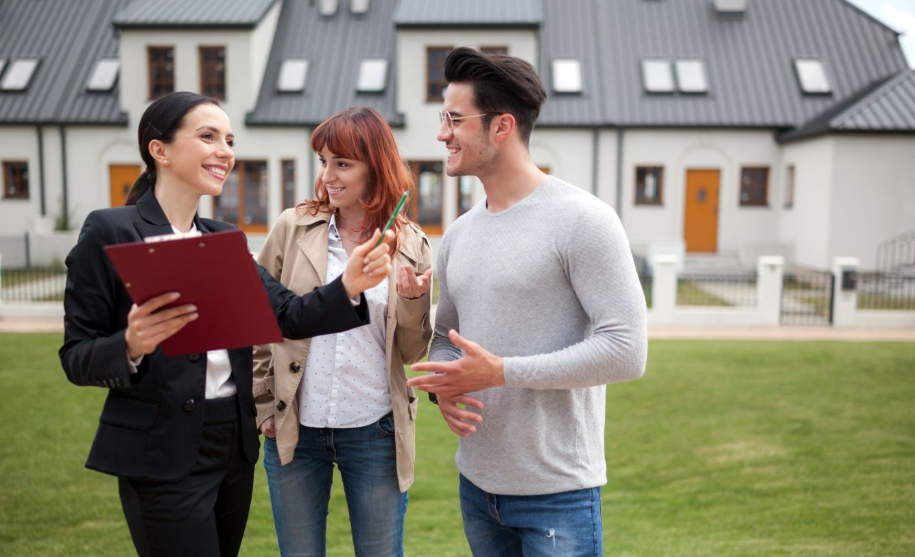 Real estate agent showing potential property to young couple