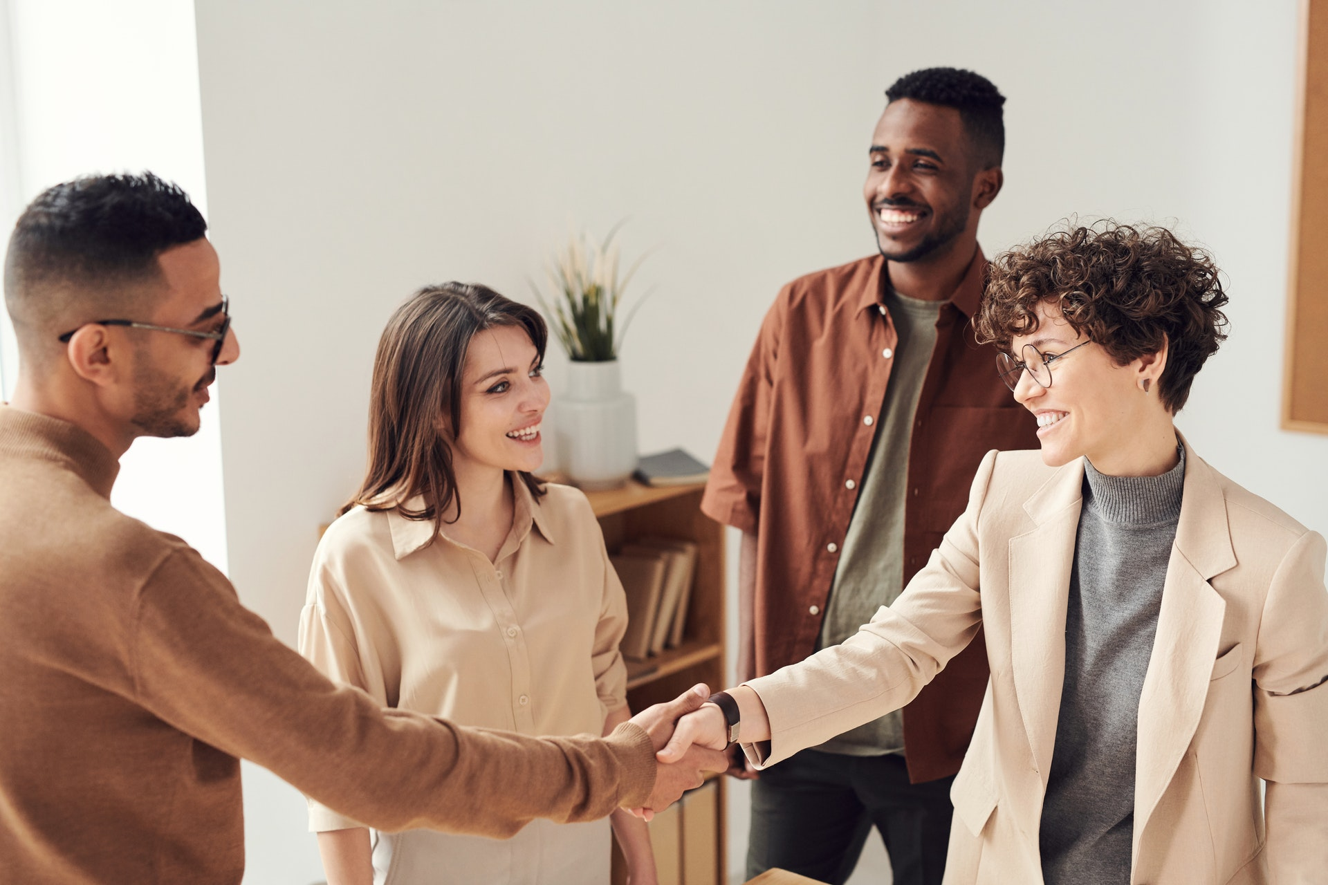 Real estate agents shaking hands of clients and smiling
