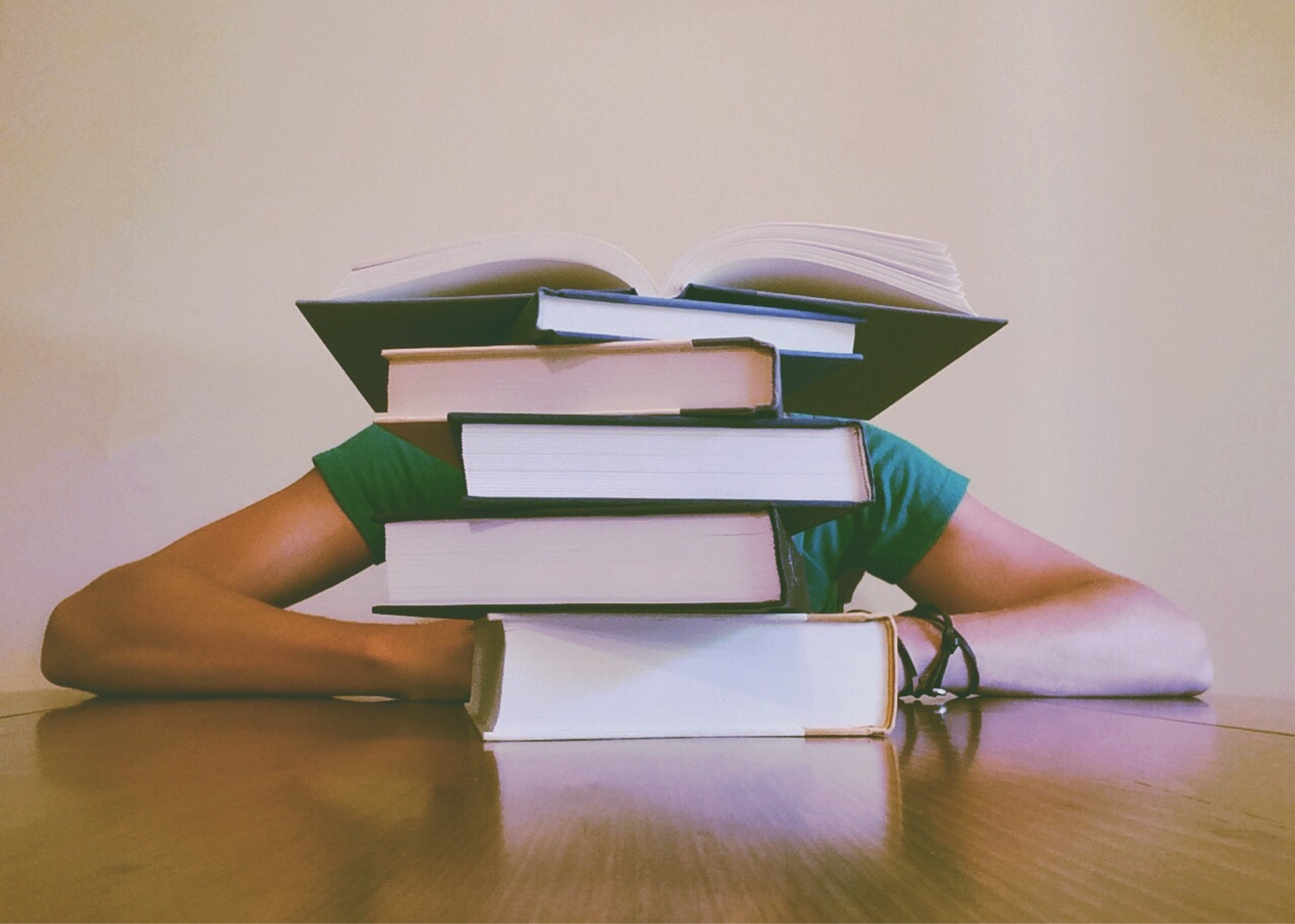 Real estate school student sitting in front of stack of textbooks