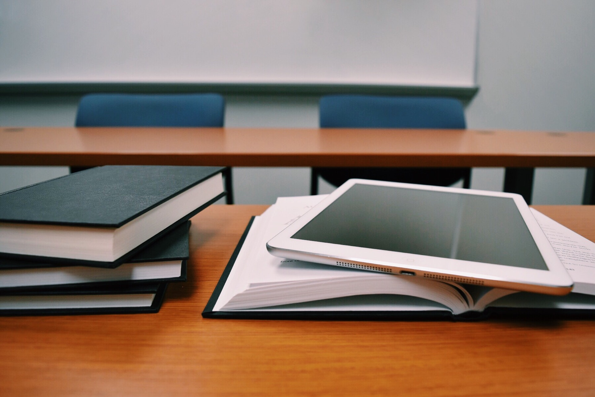 Real estate textbooks and ipad on desk inside of classroom
